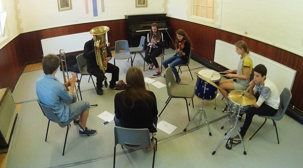 Seven musicians learning improvisation on various instruments.