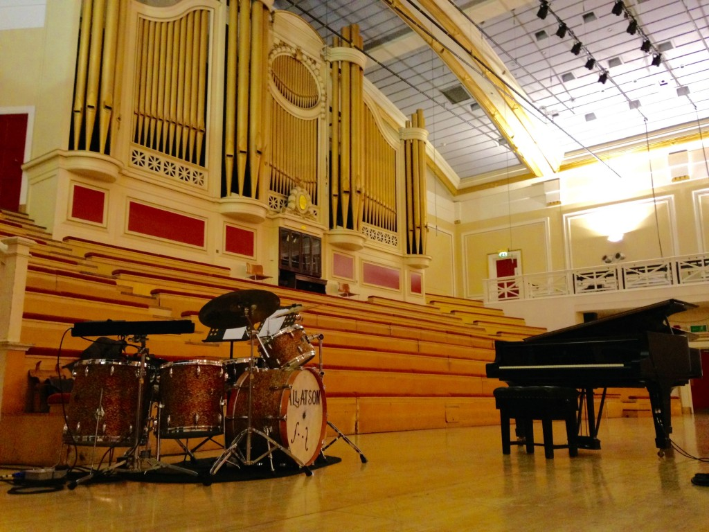 De Montfort Hall concert stage with pipe organ, piano and drum set.