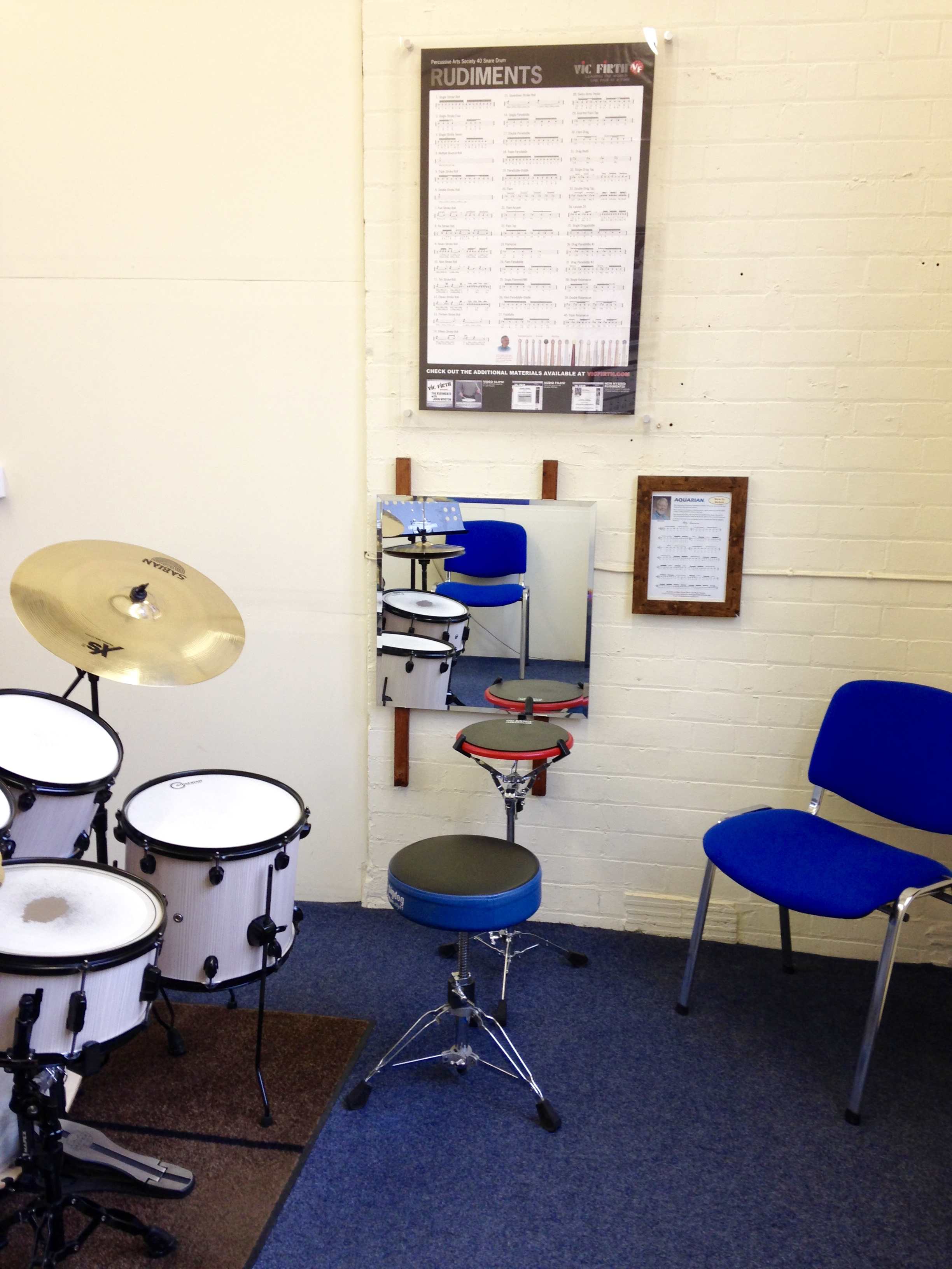 Aquarian practice pad, wall-mounted mirror and drum rudiment chart set up in Studio 1.